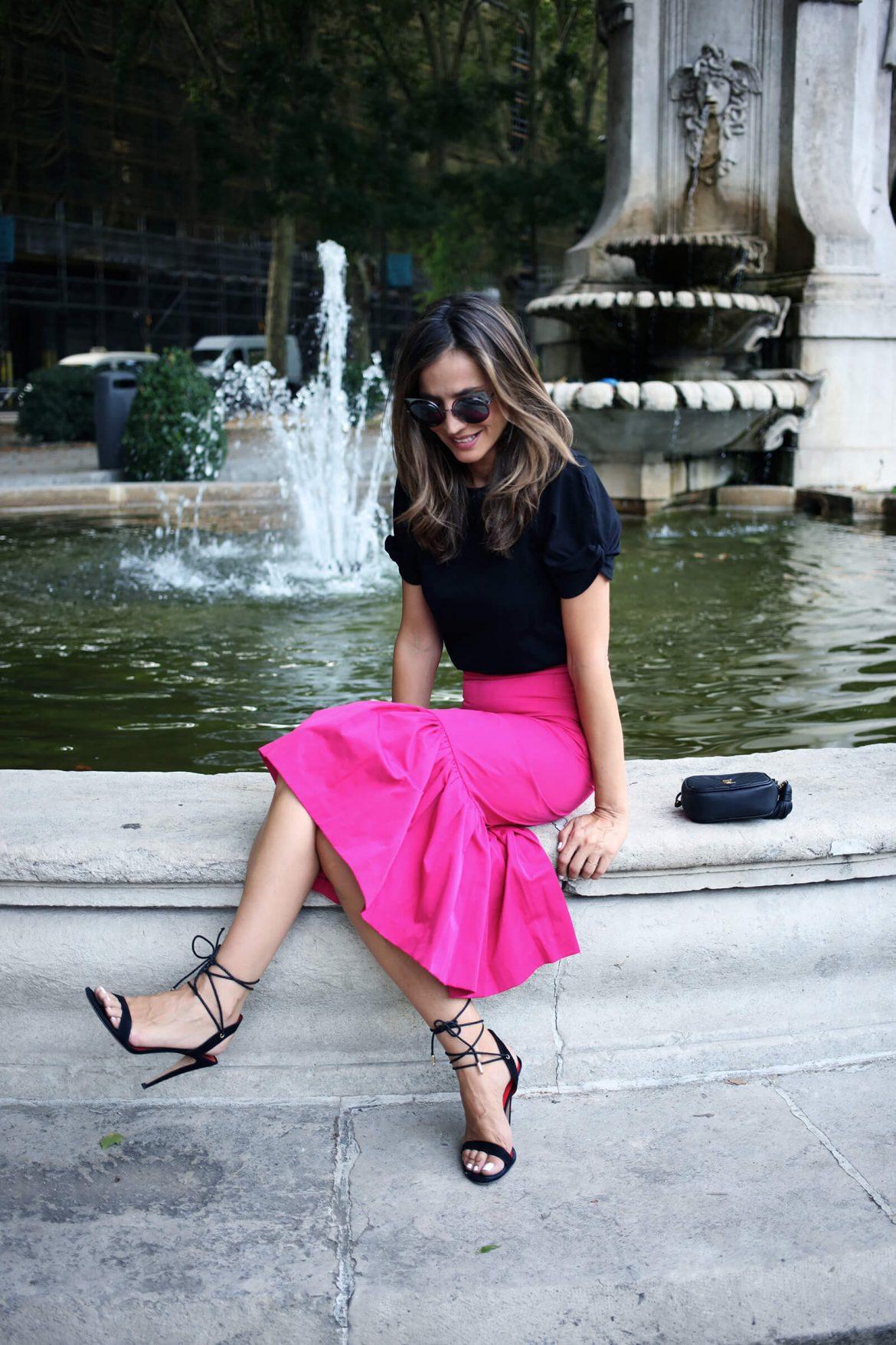 Sandalias negras pura lopez con cordones atados al tobillo, outfit verano combinado con falda de volantes fucsia