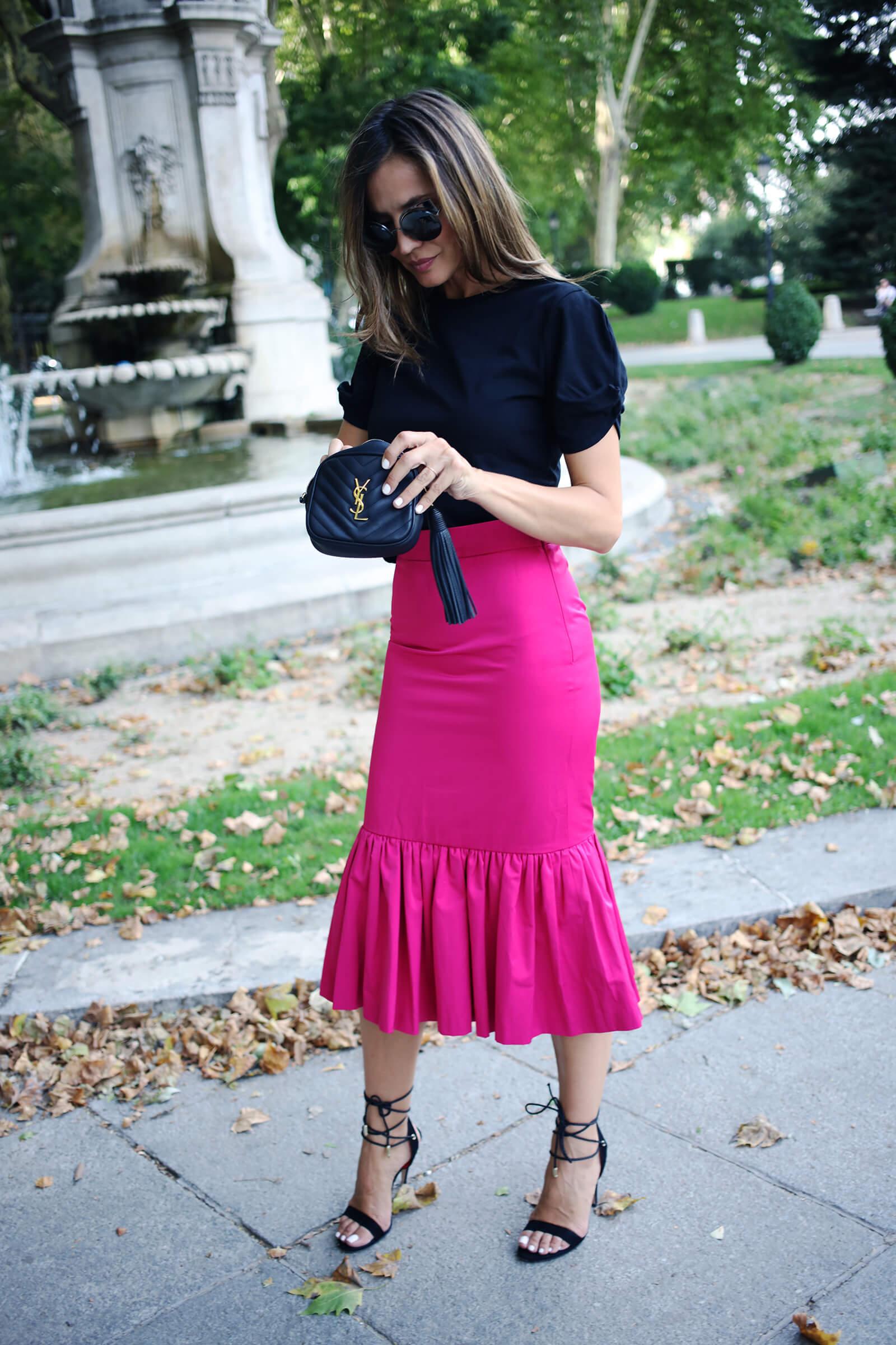 falda fucsia combinada con sandalias negras de tiras