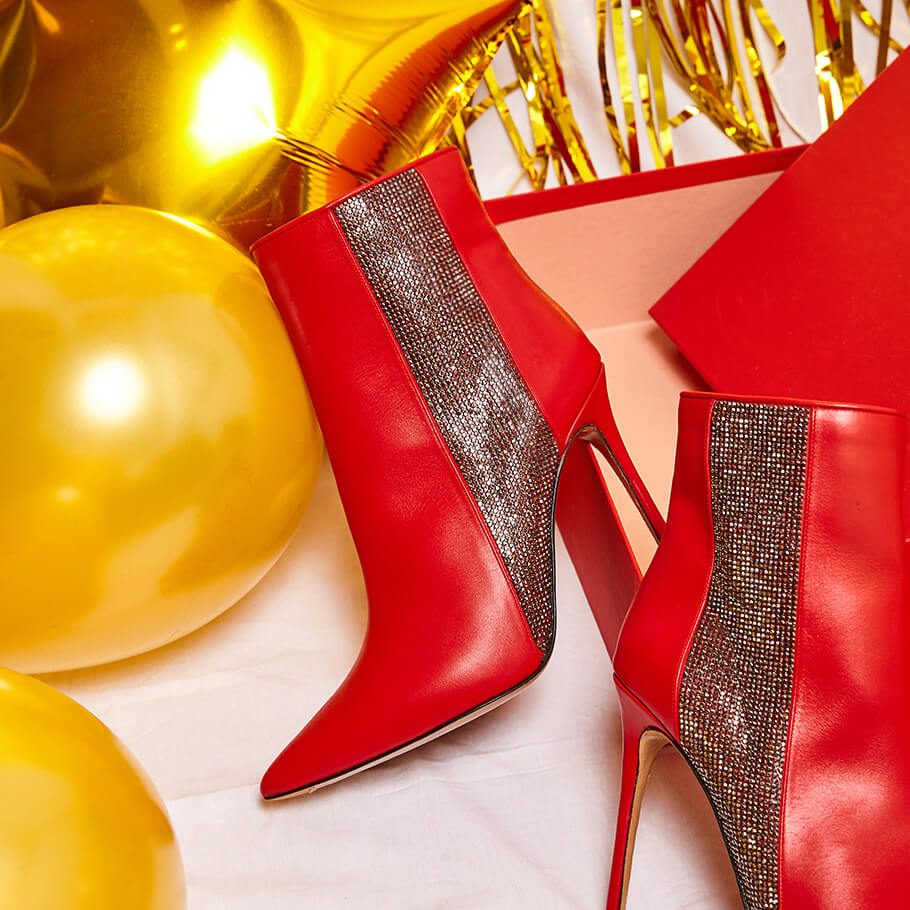 High heel point-toe ankle boots in red leather with strass panel
