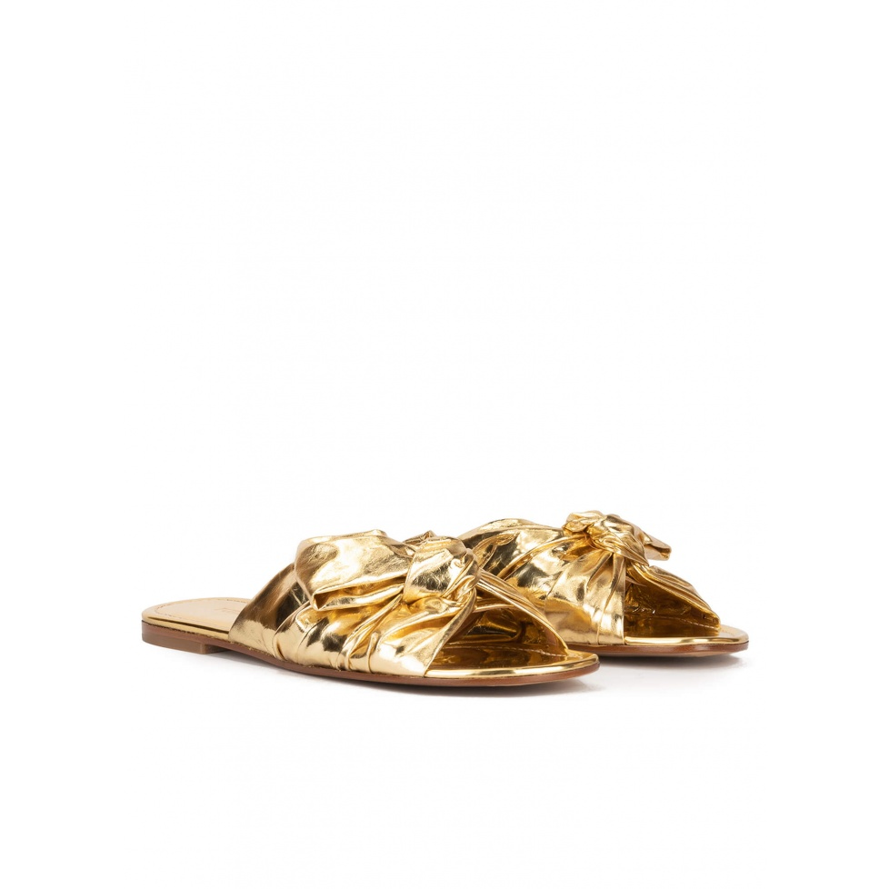 Gold flat sandals with bow detail