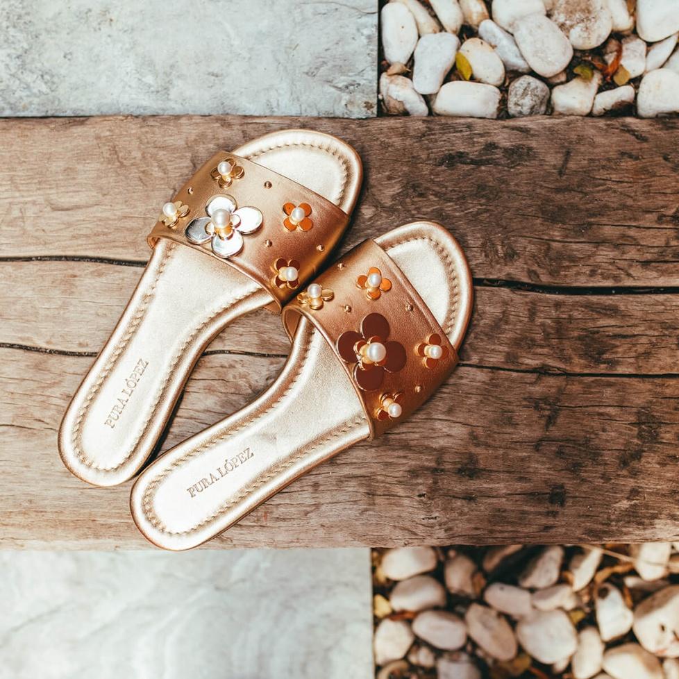 Flower-embellished flat sandals in golden metallic leather