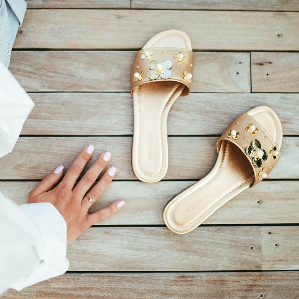 Sandalias planas metalizadas en piel dorada con adorno de flores