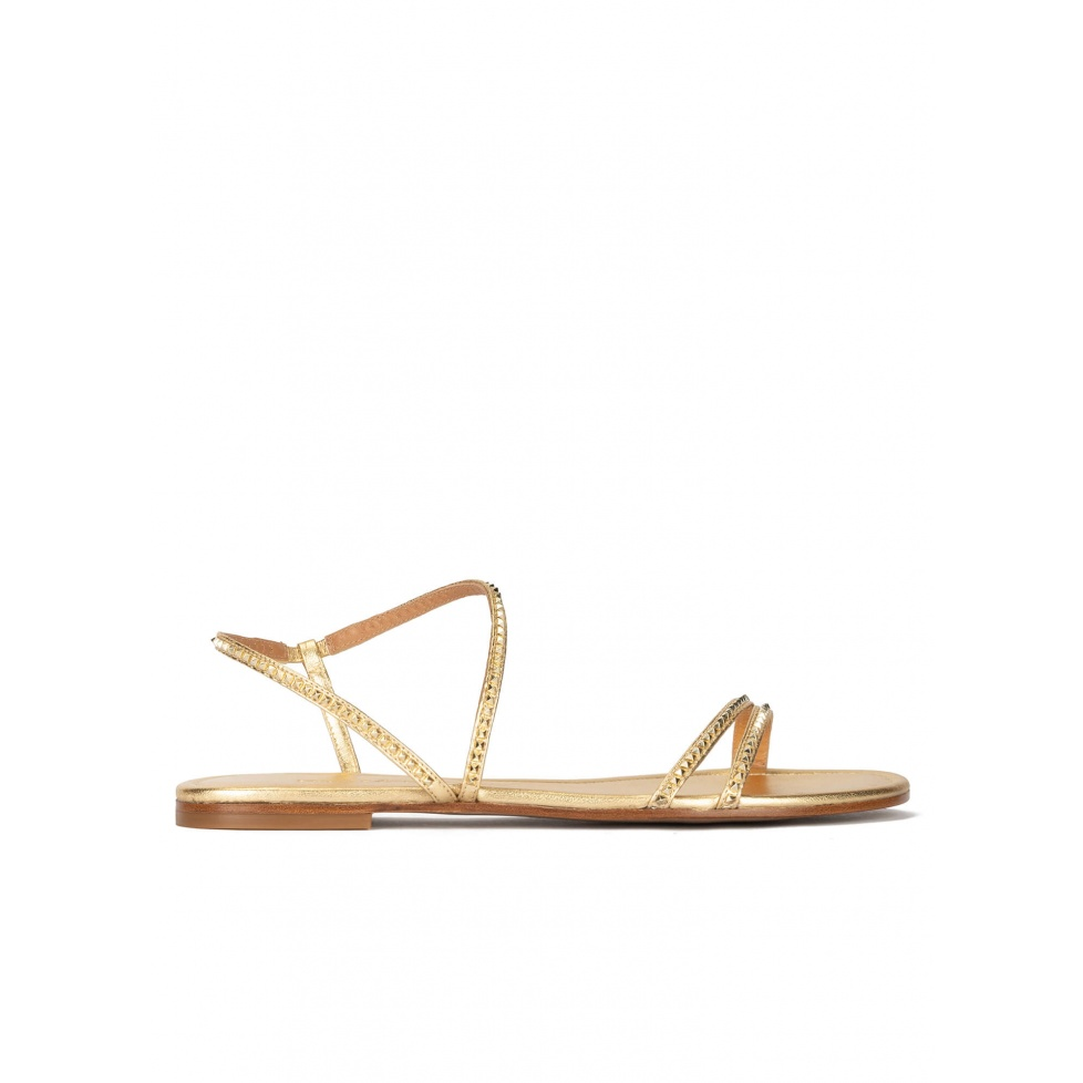 Golden strappy flat sandals in leather with pyramid studs