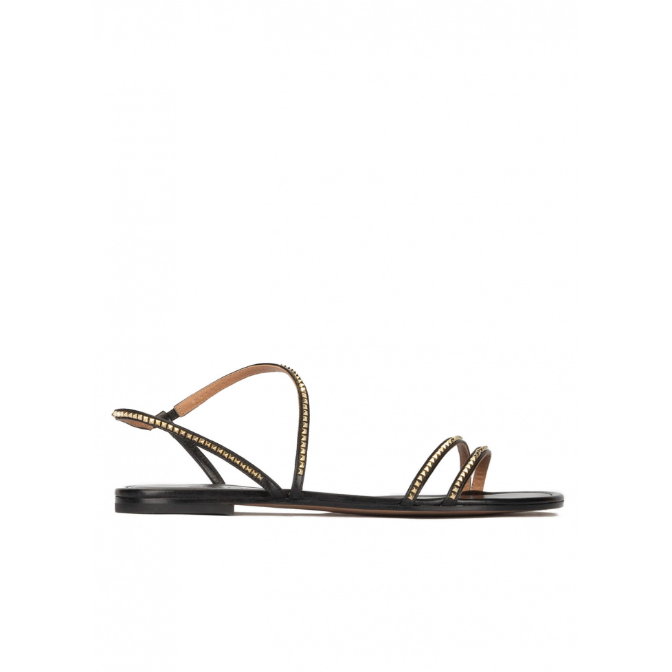 Strappy flat sandals in black leather with golden studs