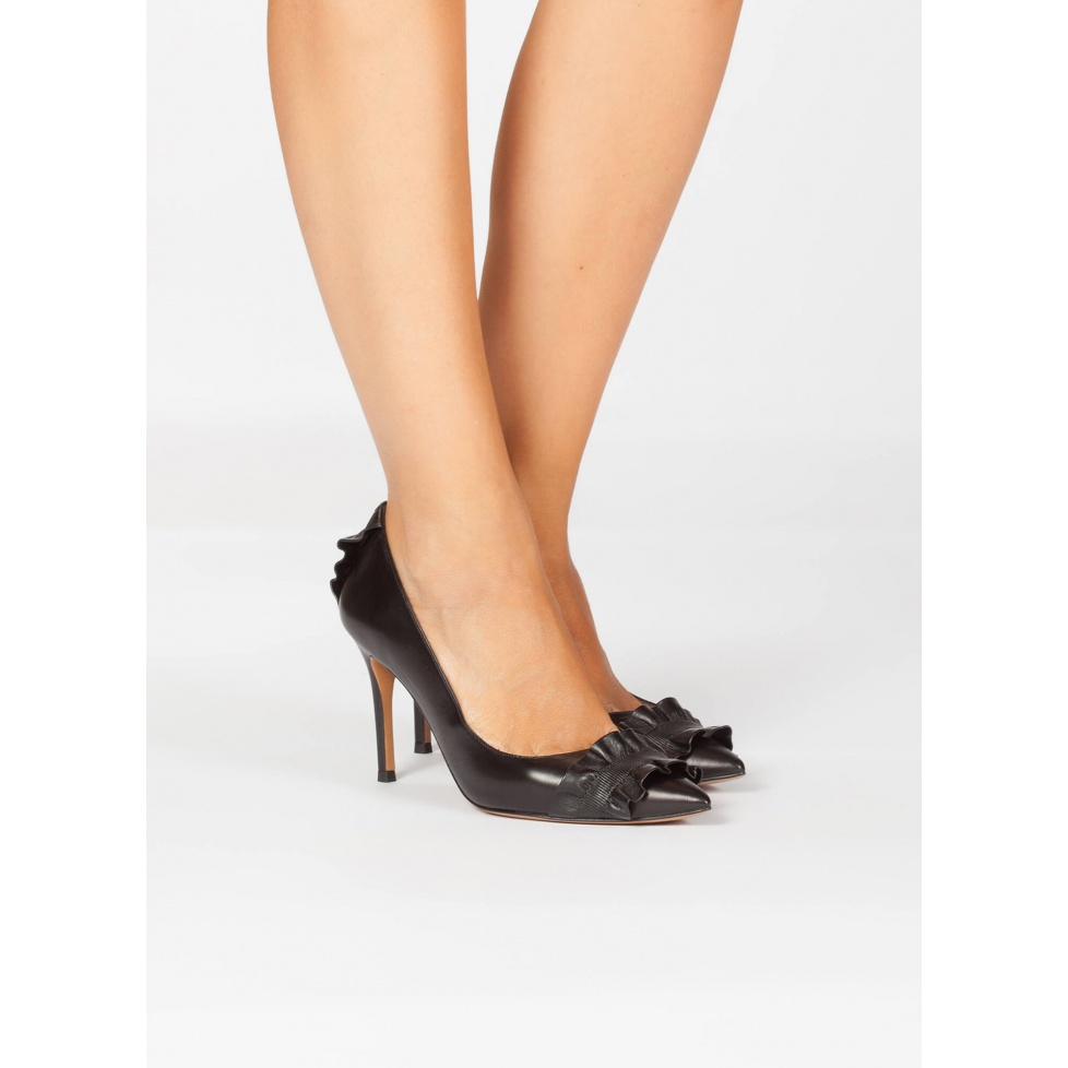 Black leather point-toe shoes with ruffle details