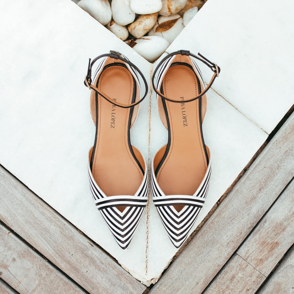 Ankle strap point-toe flats in black and white leather